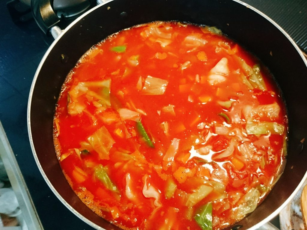 トマト缶を加えて煮る